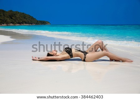 Beautiful sexy woman in black bikini lying on exotic tropical beach beside blue water by seashore. Summer vacation. Sun tanning girl on white sand. - stock photo