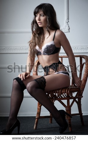 Beautiful sexy woman in erotic lingerie with wicker chairs at a white wal - stock photo