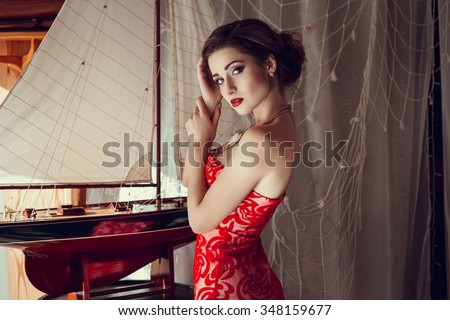 Beautiful sexy woman in restaurant cafe girl rich stylish lady resting at retro villa hotel with hairstyle makeup jewelry in evening dress. Interior and street photography - stock photo