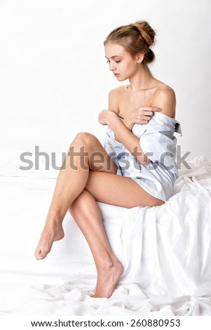 Beautiful sexy woman in shirt sitting on white bed. Studio shooting with white background. - stock photo
