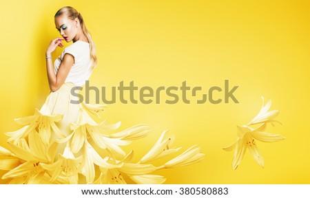 beautiful sexy woman in yellow flower dress on yellow background - stock photo