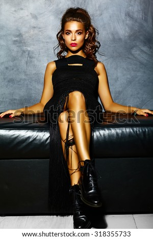Beautiful sexy woman model  lady with red lips in black elegant dress sitting on sofa  near gray wall  - stock photo