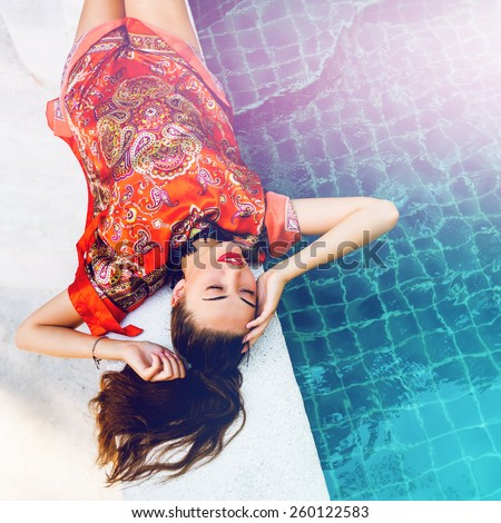 Beautiful sexy woman relaxed near pool after spa, having fun at her vacation in luxury resort, wearing stylish elegant bright beach dress. Instagram colors. - stock photo