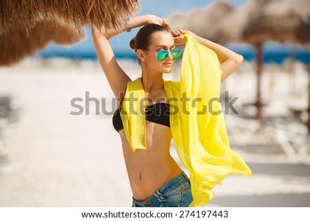 Beautiful sexy woman relaxing on the beach - outdoors. Young tanned woman on the beach in bikini and sunglasses. Young pretty hot sexy woman on the tropic island in summer near the sea - stock photo