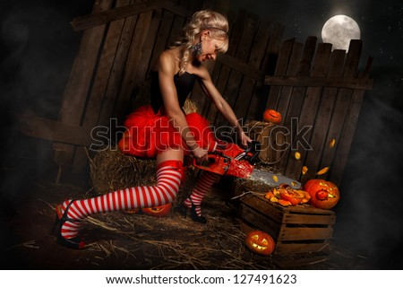 Beautiful sexy woman with halloween pumpkin against wooden background - stock photo