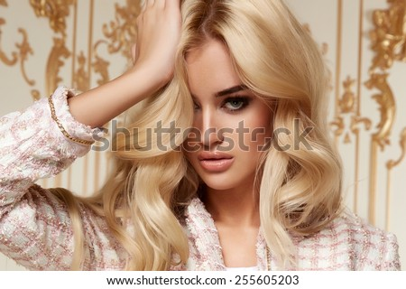 Beautiful sexy young blonde girl with long thick wavy hair thin slender figure perfect body and pretty face make-up wearing a light pink suit delicate high heels - stock photo