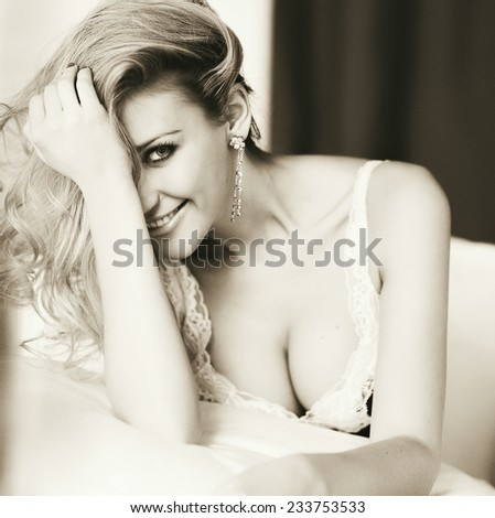 Beautiful sexy young blonde girl with puffy Breasts smiles, sepia - stock photo