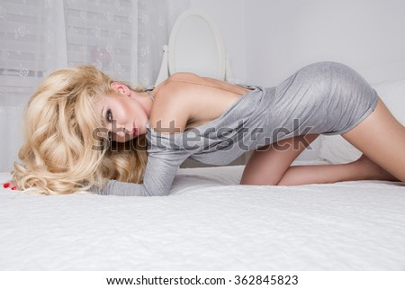 Beautiful sexy young blonde model with long curly hair lying in the bedroom on the bed of the senses in a gray dress with open back, with a big neck back and looks at the camera sensually - stock photo