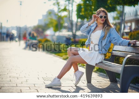 Beautiful sexy young blonde woman with long wavy hair thin slender figure perfect body and pretty face make-up wearing in a white vintage suit and a blue jeans jacket . summer accessory,pink backpack  - stock photo