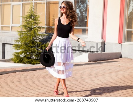 Beautiful sexy young brunette girl with long thick wavy hair thin slender figure perfect body and pretty face make-up wearing a light pink suit delicate high heels.Walk on the street in casual style - stock photo