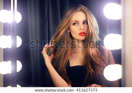 Beautiful sexy young caucasian woman looking into makeup mirror at herself and enjoying her time. Red lips, blue eyes. Fashion portrait. - stock photo