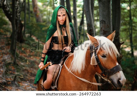 Beautiful sexy Young Female elf  with a bow on horseback  - stock photo