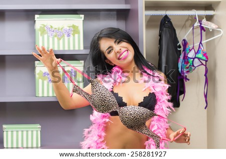 beautiful sexy young girl wearing underwear searching for clothes trying a bra in her closet - stock photo