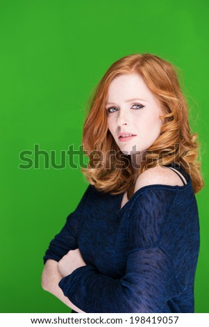 Beautiful sexy young redhead woman in a stylish off the shoulder top standing sideways with folded arms giving the camera a sultry look - stock photo