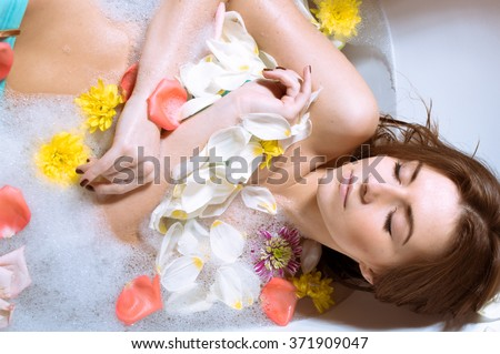 Beautiful sexy young woman having bath with flower petals - stock photo