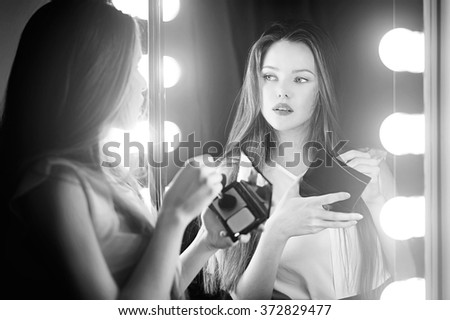 Beautiful sexy young woman looking into a mirror at herself and use cosmetic brush powder on her face. - stock photo