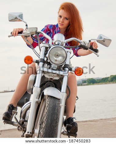 Beautiful, sexy, young woman on a motorcycle. - stock photo