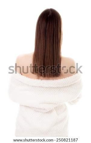 Beautiful sexy young woman taking off white bathrobe, undress exposing shoulders, isolated. Cozy, beauty, comfort, wellbeing, healthcare, bodycare concepts - stock photo