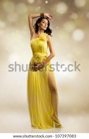 beautiful sexy young woman wearing yellow evening dress - stock photo