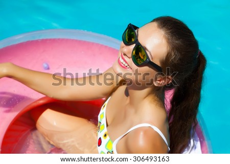 Beautiful sexy young woman with perfect slim figure with long dark hair and wet bathing suit fashion in stylish glasses from the sun is sunning by swimming pool swim, sunbathe have fun at pool party - stock photo