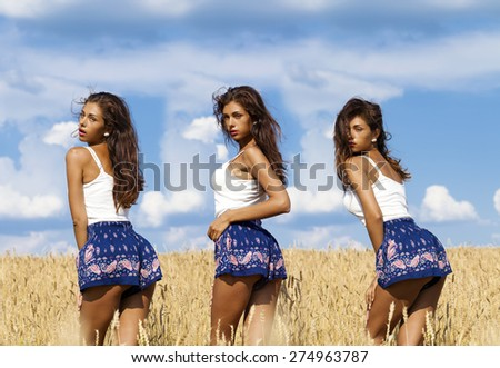 Beautiful sexy young women in blue skirt in a wheat golden field - stock photo