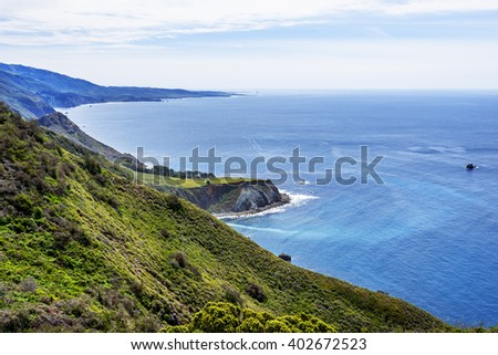 Beautiful shimmering blue sea, ocean, and white puffy clouds, along steep sheer jagged cliffs, near ragged Point, CA. traveling the Big Sur Highway (Highway 1), on the California Central Coast. - stock photo