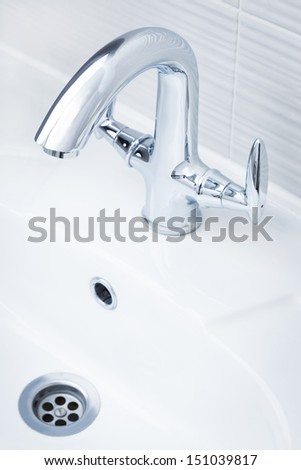beautiful shiny faucet and white sink - stock photo