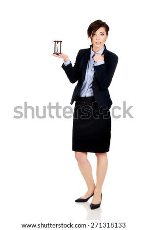 Beautiful shocked businesswoman holding hourglass. - stock photo