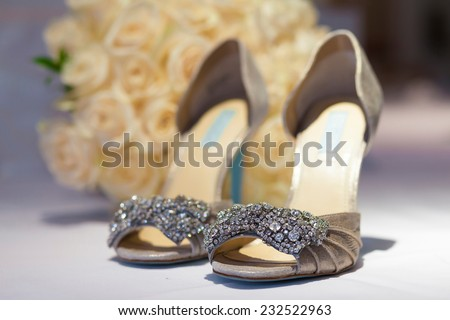 Beautiful shoes from bride in front of flowers - stock photo