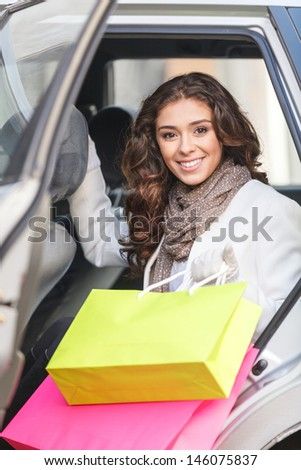 Beautiful shopping addict. Beautiful young women sitting on the back seat of the car and holding the shopping bags - stock photo