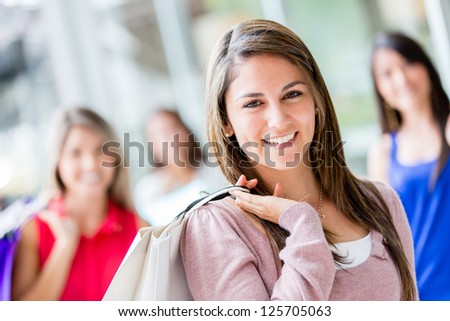 Beautiful shopping woman with her friends smiling - stock photo