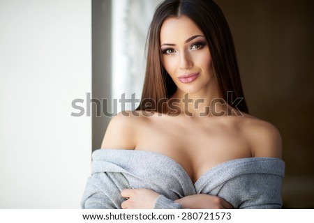 Beautiful showy girl with plump lips and big Boobs in gray soft sweater with bare shoulders and bare back standing near the window. Sexy, shy lady - stock photo