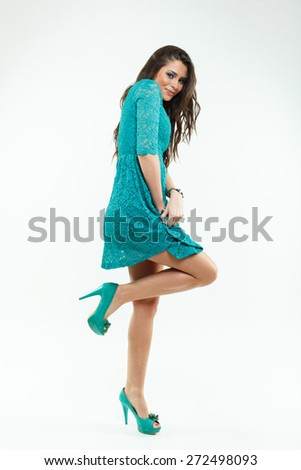 Beautiful shy young woman in a green dress on white background - stock photo