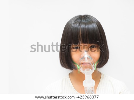 Beautiful sick girl inhalation therapy by the mask of  inhaler . Close up image of a cute kid with respiratory problem or asthma. View of sick girl with oxygen mask.  Clear mask for curing respiratory - stock photo