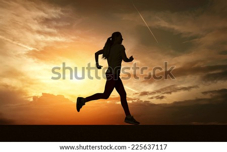 Beautiful silhouette of female running on road under sky with sun light - stock photo