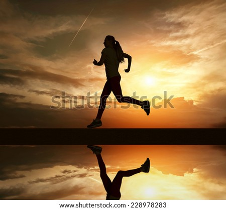Beautiful silhouette of female running on road under sky with sun light and reflection in water - stock photo