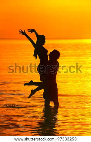 Beautiful silhouette of male holding young girl against sea sunset. - stock photo