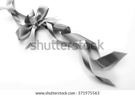 Beautiful silver bow with curly ribbons isolated on white background - stock photo