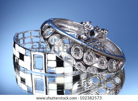 Beautiful silver bracelets on blue background - stock photo