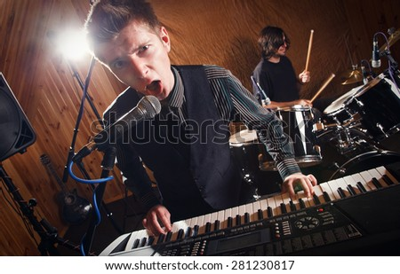 beautiful singer keyboard player sings into a microphone - stock photo