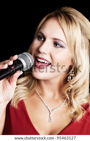 Beautiful singer with microphone on a black background - stock photo