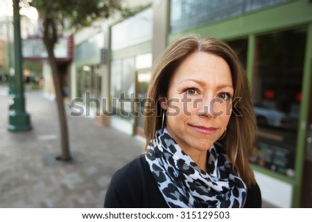 Beautiful single Caucasian business woman outdoors in front of store - stock photo