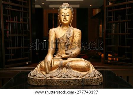 Beautiful sitting golden Buddha sculpture in a prayer hall. Statue of sitting golden Buddha - stock photo
