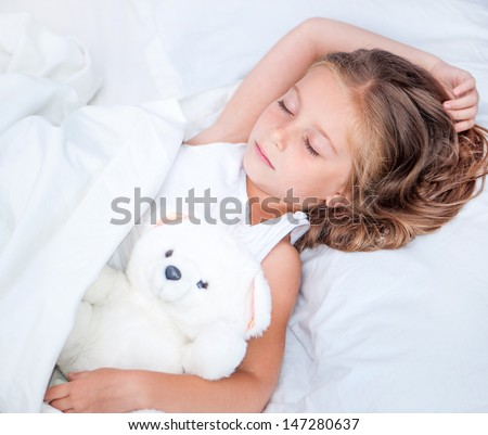 beautiful six year old girl sleeping in the bed with her teddy bear - stock photo