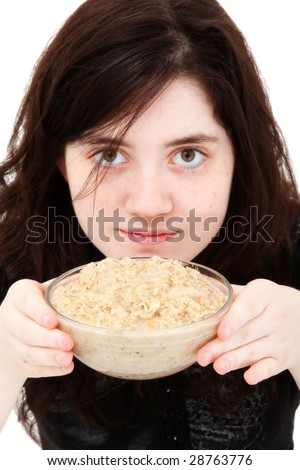 Beautiful sixteen year old girl with bowl of oatmeal (porridge) over white. - stock photo