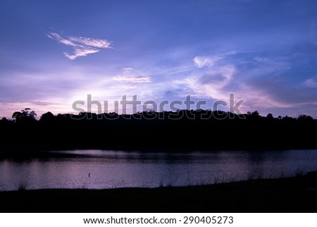 Beautiful sky landscape with sunset over river bank - stock photo