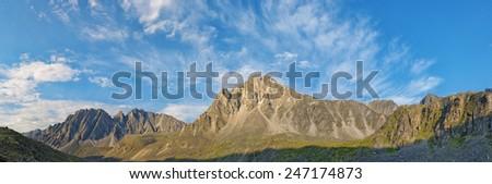 Beautiful sky over the mountain peaks in July. Eastern Sayan. Siberia - stock photo
