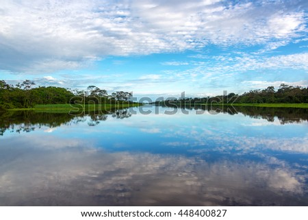Beautiful sky reflected in a river in the Amazon rain forest near Iquitos, Peru - stock photo