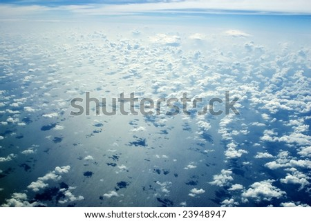 Beautiful skyscape over Indian Ocean. Blue sky with many single clouds below, just above ocean water. - stock photo