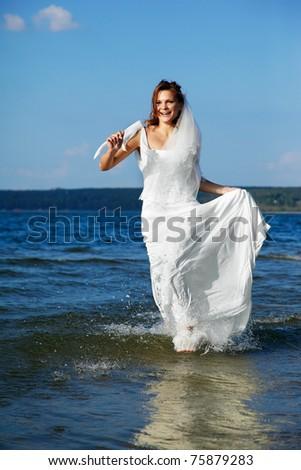 beautiful slavonic bride running in sea waves - stock photo